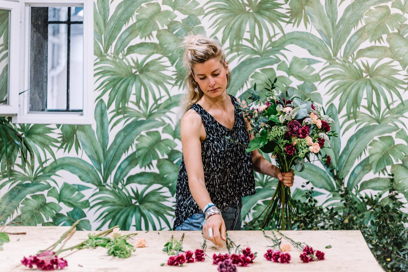 Emmanuelle Magnan de Pampa Paris présente un bouquet dans son atelier, devant un papier peint à feuilles vertes